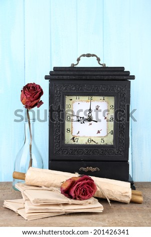 Still life with old retro clock on blue wooden background - stock photo