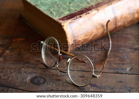 Still life with old spectacles near book on wooden table - stock photo