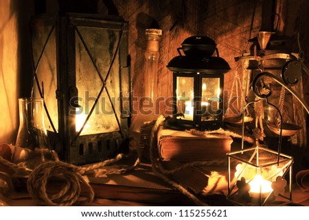 Still life with old things - old lamps, books on wooden background - stock photo