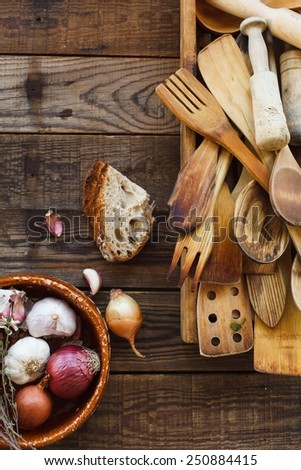 Still life with old wooden kitchen accessories, onions and bread onto an vintage surface.  Kitchen wooden utensil of scapula, spoon and fork on wooden table. Natural old food concept . Top view.  - stock photo