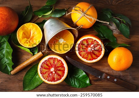 Still life with orange fruit and green leaves on wooden table. Top view.  - stock photo