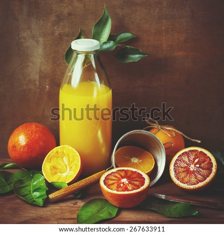 Still life with orange fruit and juice on wooden table. Painting style. Selective focus. Instagram color effect. - stock photo