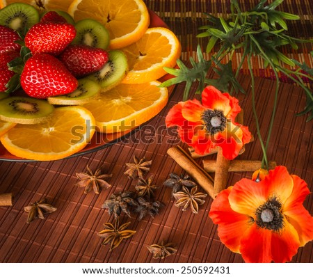 Still life with oranges, kiwi, strawberry, cinnamon, anise and poppies - stock photo