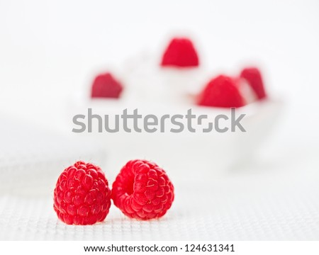 Still life with pair of raspberry on white linen table cloth, copy space design ready - stock photo