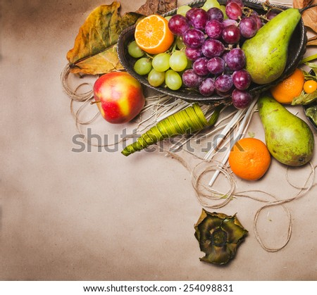 Still life with pears, apple, grapes, tangerines, physalis with dry leafs, twine, decorations and silver bowl on light brown paper. View from the top - stock photo