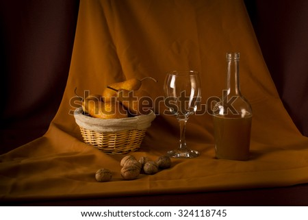 Still life with pears, glass, organic wine bottle and walnuts