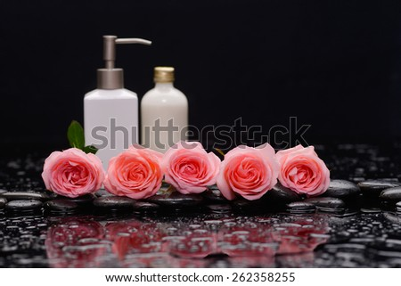 Still life with pink five rose and massage oil on wet stones - stock photo