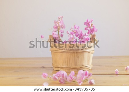 Still life with pink flowers on wooden table over grunge background, Valentine concept