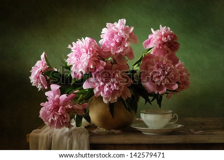 Still life with pink peonies and a cup of tea - stock photo