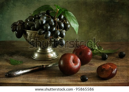 Still life with plums and grapes - stock photo