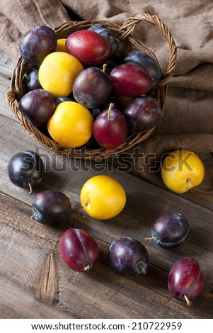 Still life with plums in a basket on the table - stock photo