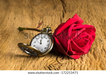Still life with pocket watch and red rose bud on grunge wooden texture - stock photo