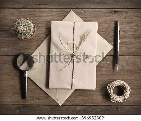 still life with postal parcel wrapped in brown paper and the contents of a workspace composed. Different objects on wooden table.sepia filter effect.Flat lay - stock photo