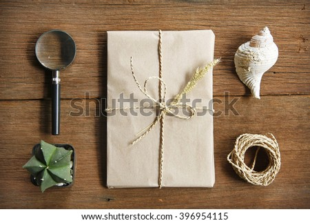 still life with postal parcel wrapped in brown paper and the contents of a workspace composed. Different objects on wooden table.Flat lay