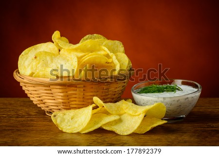 still life with potato chips and dill dip sauce - stock photo