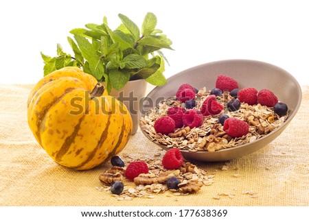 Still life with pumpkin, raspberries, walnuts, peppermint and muesli - stock photo