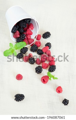 Still life with raspberries and blackberries - stock photo