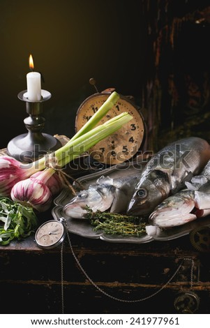 Still life with raw fish seabass, herbs, vegetables and vintage clock - stock photo