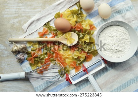 still life with raw homemade pasta and ingredients for pasta..process of cooking pasta - stock photo