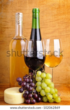 still life with red and white wine, grapes and cheese on a wooden background