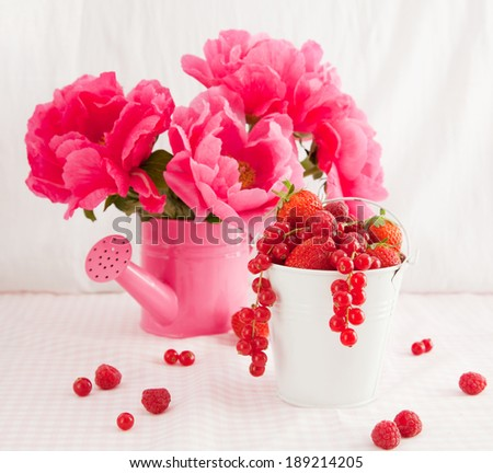 Still life with red berries and peonies - stock photo