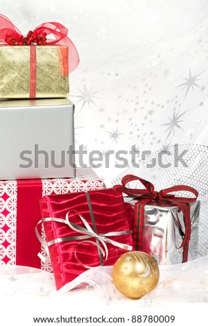 Still life with red, silver, gold wrapped Christmas gifts, pretty ribbons and ornaments. Silver star translucent fabric backdrop on white. Vertical format with copy space. - stock photo