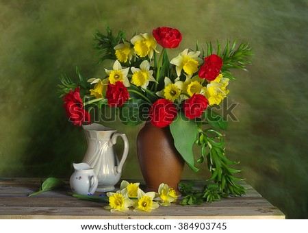 Still life with red tulips and daffodils .Bouquet with spring flowers in a clay vase and porcelain jugs. - stock photo