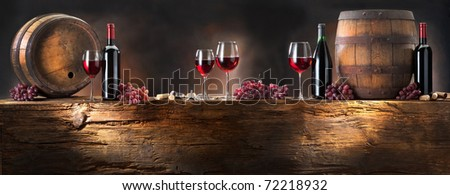 still life with red wine and barrel on old wood - stock photo