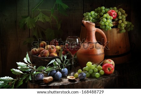 Still-life with red wine and fresh juicy fruit, fragrant red wine in a graceful glass and fresh juicy sweet apricots and plum both fragrant apples and clusters of ripe juicy green grapes - stock photo