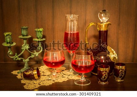 Still life with red wine and jug over wooden background - stock photo