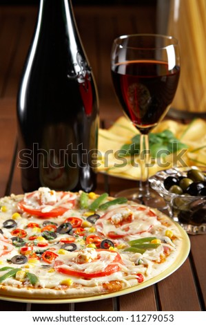 still life with red wine and pizza on the table - stock photo