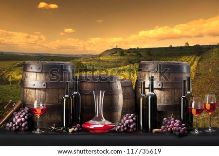 still life with red wine and vineyard - stock photo