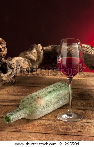 Still life with red wine glass and bottle