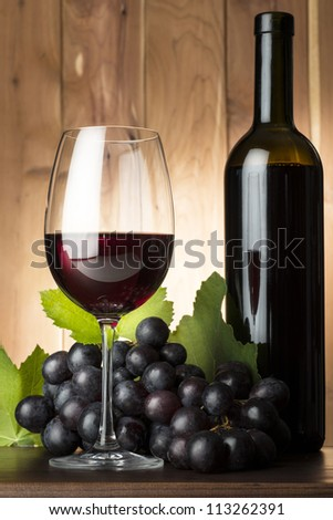 still life with red wine glass and red grape