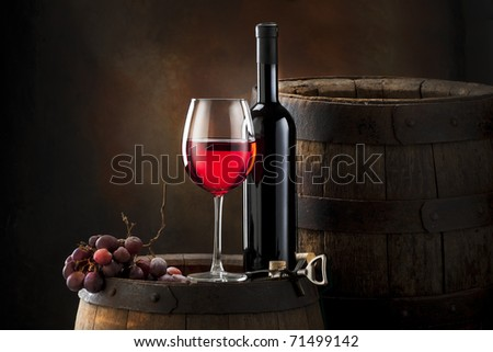 still life with red wine on old barrel - stock photo