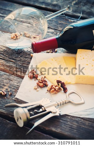 Still Life with Red Wine, Wallnuts, Cheese and Opener on Wooden Table. Rural Style - stock photo