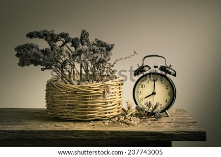 Still life with retro clock and dry flowers on wooden table - stock photo