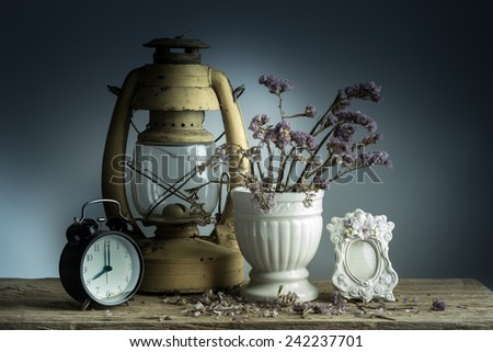 Still life with retro clock and flowers, old lamp on wooden table - stock photo