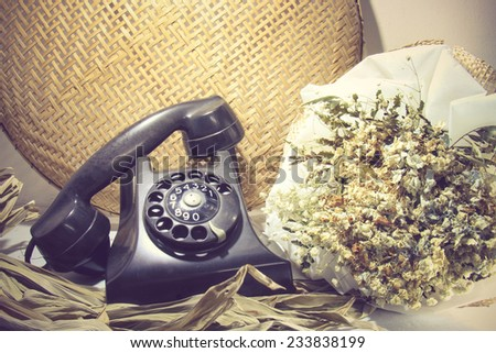 Still life with retro phone, dead flowers, toned image - stock photo