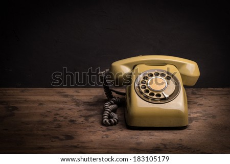 Still life with retro telephone on wooden table - stock photo