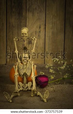 still life with romantic skeleton sitting on neck for eternal love. - stock photo