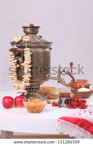 Still-life with Russian samovar, sweet jam, appetizing pancakes and a bundle of steering-wheels to pancake week celebrating - stock photo