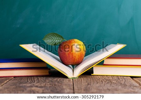 """Still life with school books and apple against blackboard with """"back to school"""" on background - stock photo"""