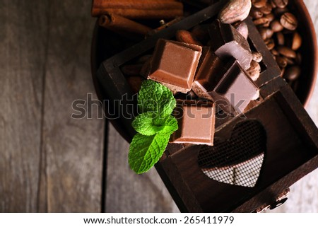 Still life with set of chocolate, coffee beans and spice on wooden table, closeup - stock photo
