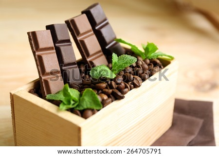 Still life with set of chocolate in wooden box of coffee grains on wooden background - stock photo
