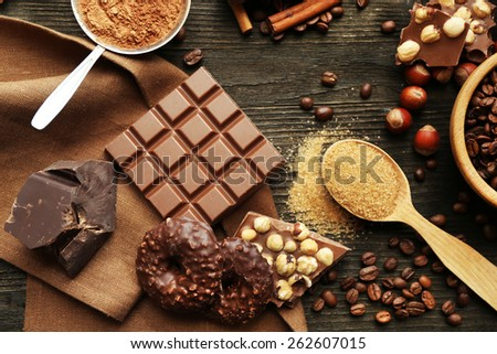 Still life with set of chocolate, nuts and spices on wooden table, top view - stock photo