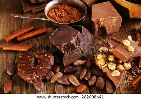 Still life with set of chocolate on wooden table, closeup - stock photo