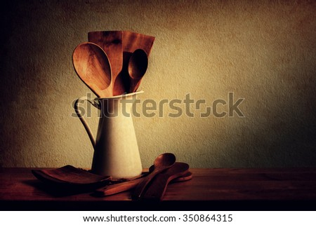 Still life with set of kitchenware with wooden ladle and wooden spoon in white vase on wooden table over grunge background