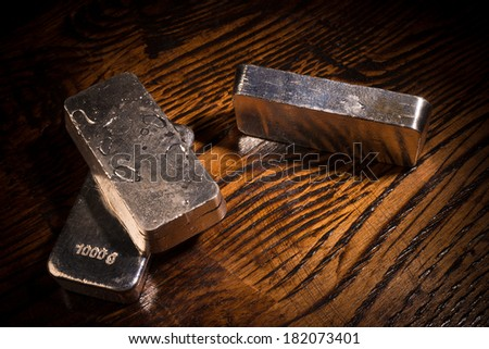 Still life with silver bars on a wooden background - stock photo