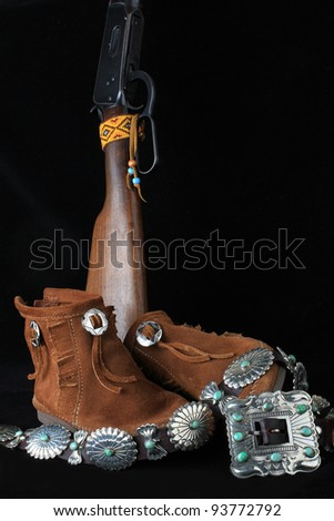 Still life with silver concho adorned leather moccasins; handcrafted silver and turquoise belt; and vintage lever-action rifle against black background. - stock photo